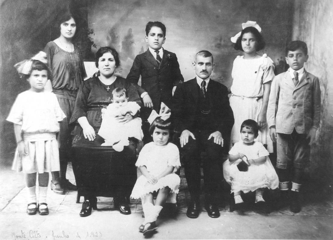 José Kairalla e Maria Amélia, em 1923, com seus oitos filhos. Os quatro mais velhos em pé (da esquerda para a direita): Olinda, Michel, Olga e Waldomiro. Alice está em pé, ao lado da mãe que segura no colo o caçula João. Ao lado do pai está Odete (segurando uma bolsinha) e, ao centro, Nelly entre a mãe e o pai.